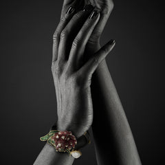 Woman wearing Black Wood bangle with Pink tourmaline, Pearl & Tsavorites