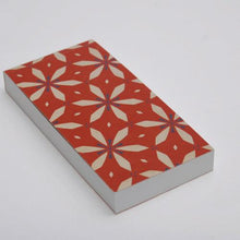 Notepad with perforated sheets and red flower pattern cover