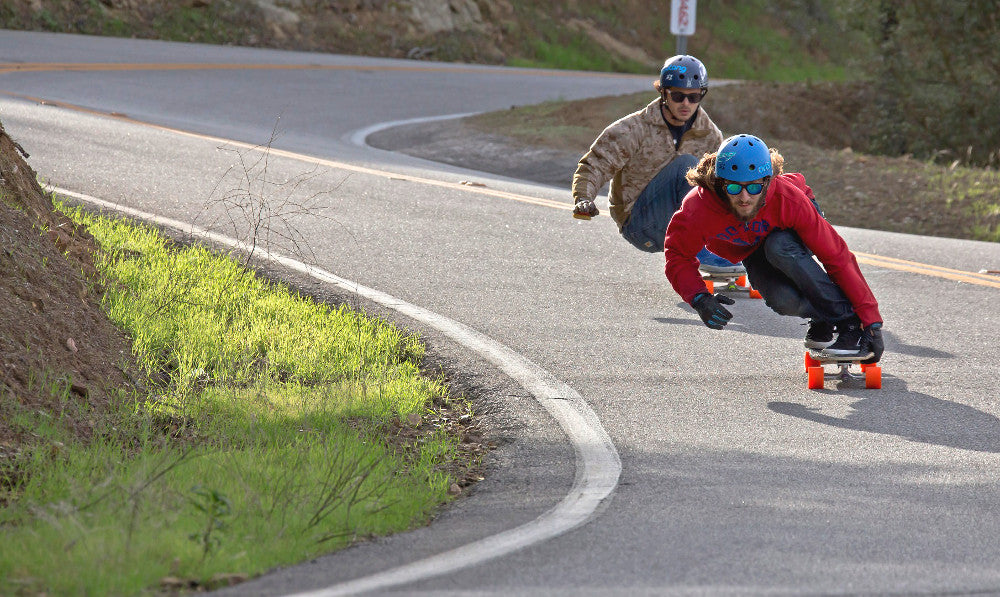 Couple of guys going downhill and thinking about what's the best longboard wheel.