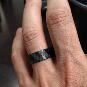 A ultra thin carbon fiber glow ring on a hand