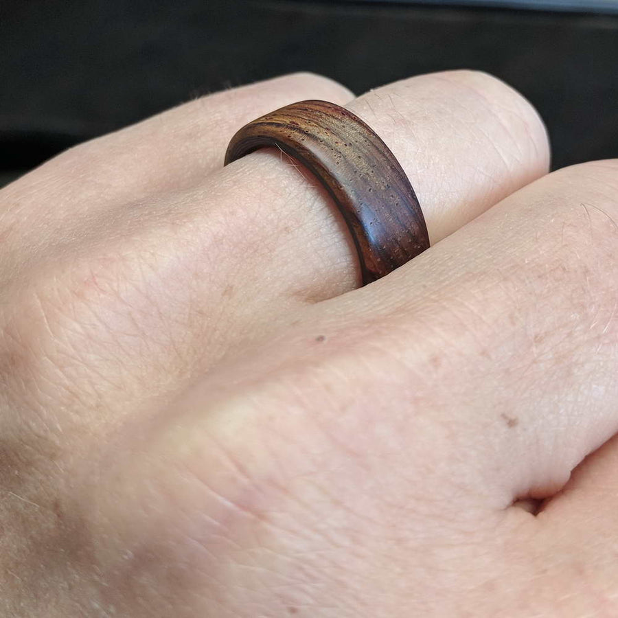 Cocobolo wood ring with carbon fiber ring on hand