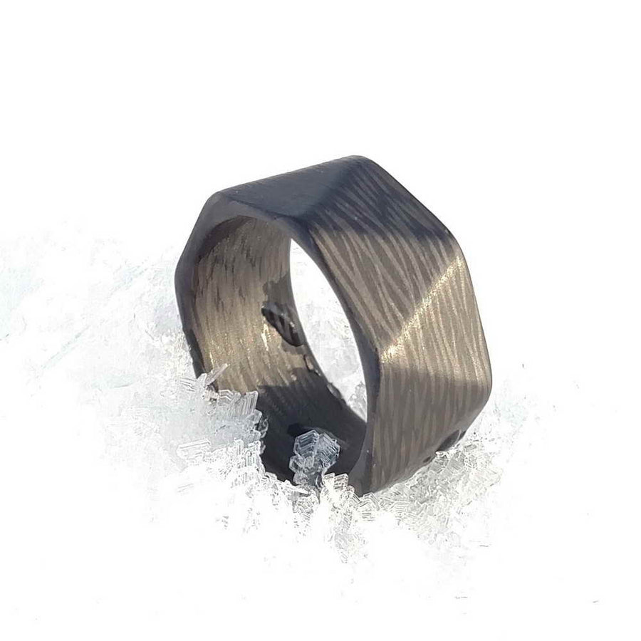 A carbon fiber ring with multiple faces in the snow