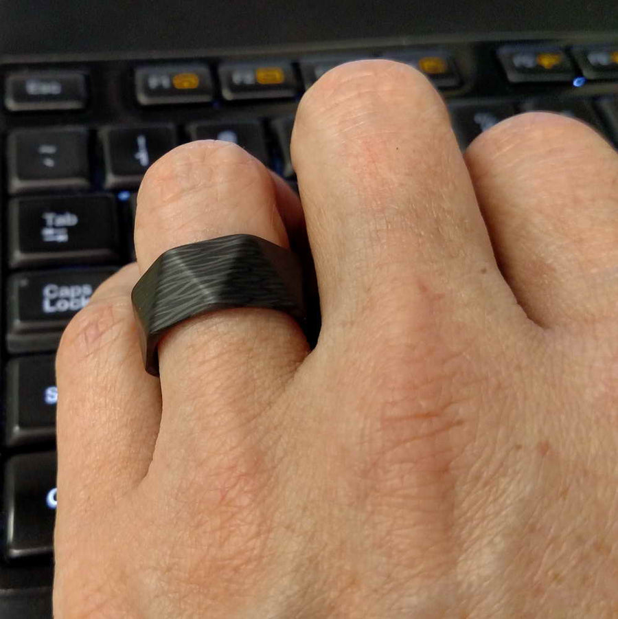 The Facet wave carbon fiber ring on a hand