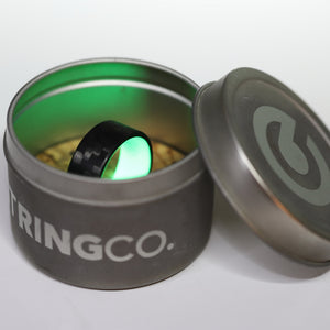 A green carbon fiber glow ring in a tin while glowing
