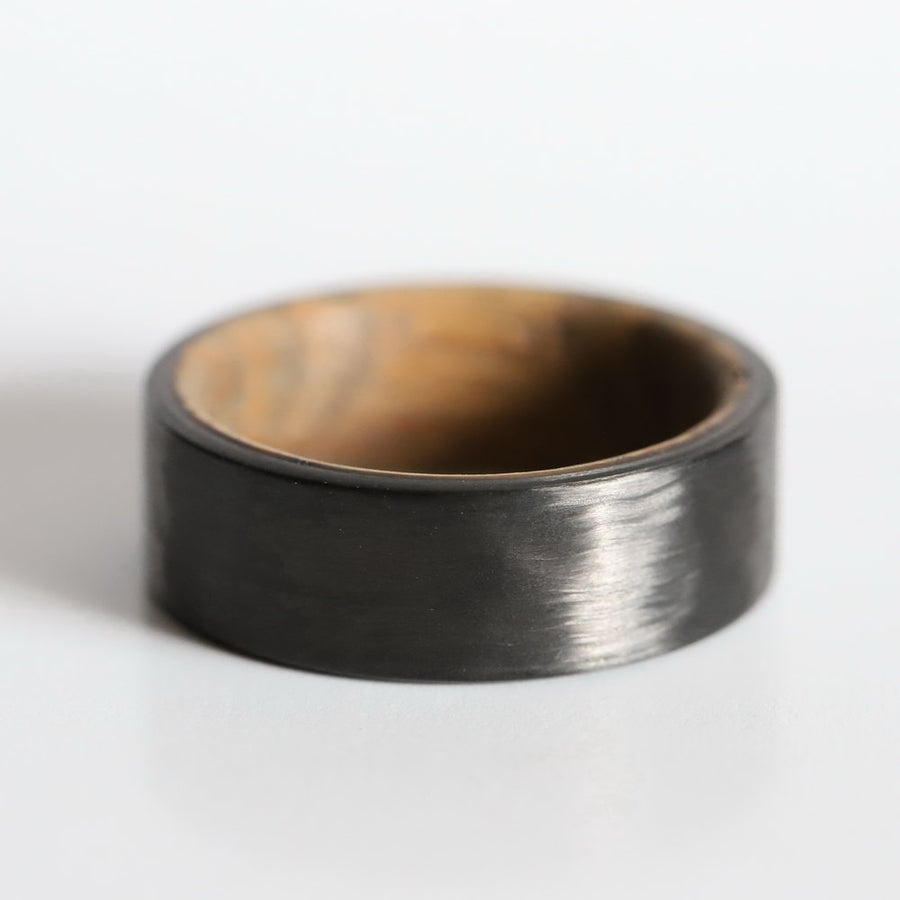 A carbon fiber wedding ring with whiskey barrel wood