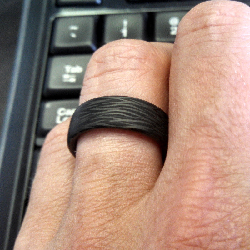 A hand wearing our minimalist carbon fiber ring featuring a wave pattern