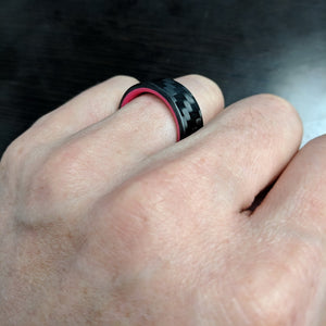 A red carbon fiber glow ring on a hand making a fist