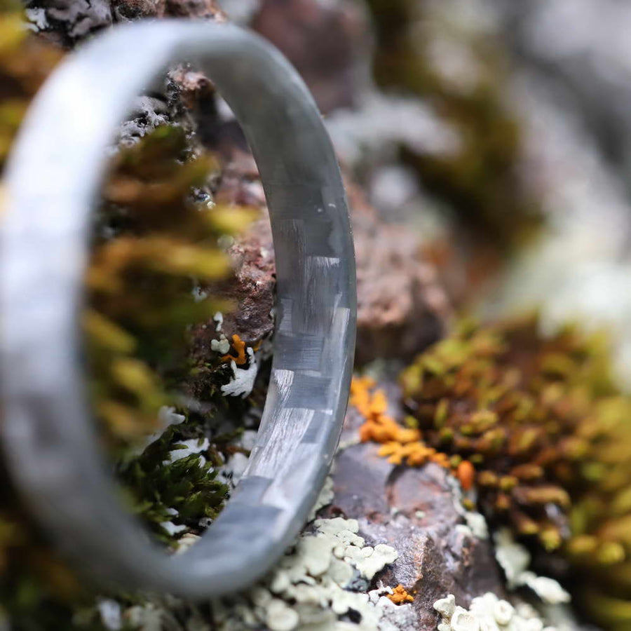 A silver fiberglass ring made designed to be a stackable ring