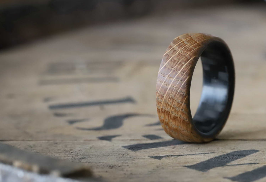 A carbon fiber ring with whiskey barrel wood