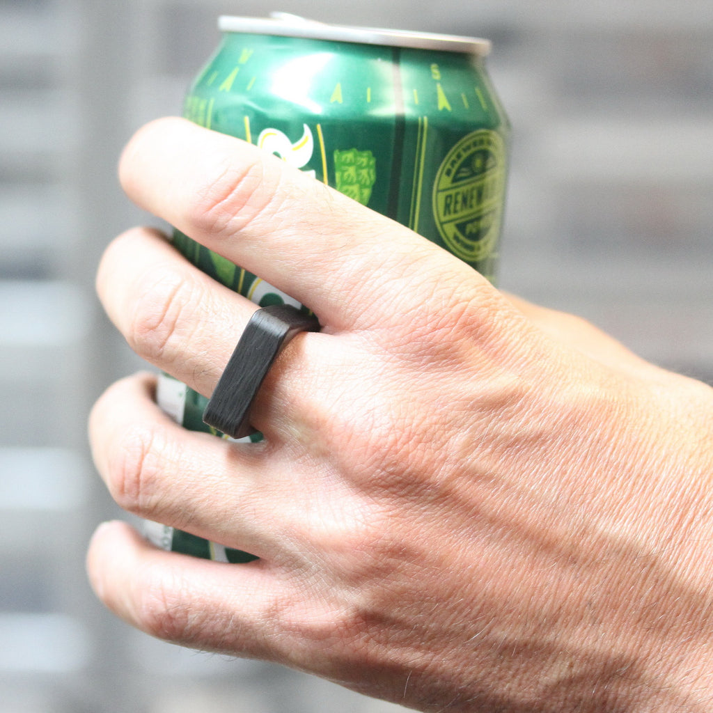 A square carbon fiber ring on a hand holding a beer