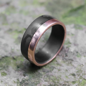A men's wedding ring with carbon fiber and rose gold