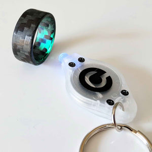 A micro uv key chain light shining on a carbon fiber glow ring