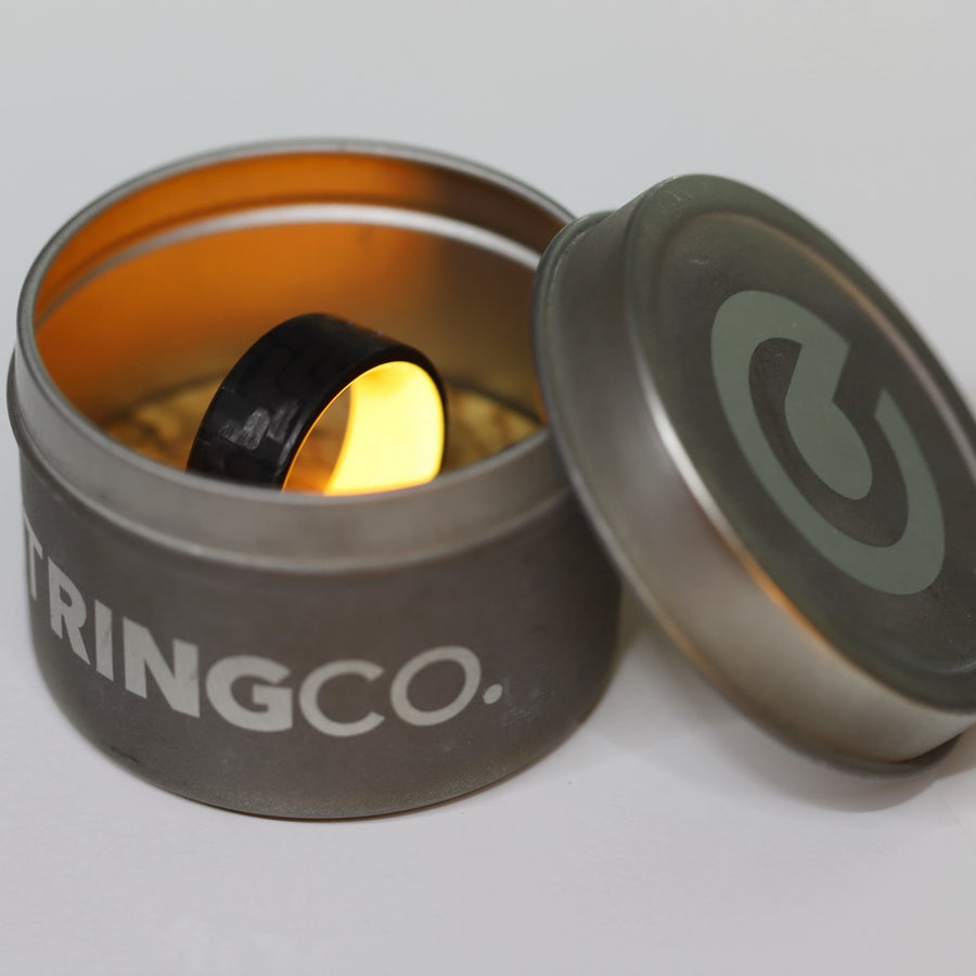 A glowing orange carbon fiber ring in a shipping tin