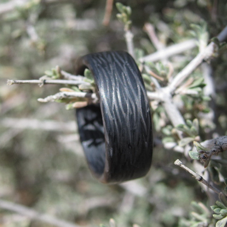 A lightweight carbon fiber ring featuring a wave pattern held by a twig