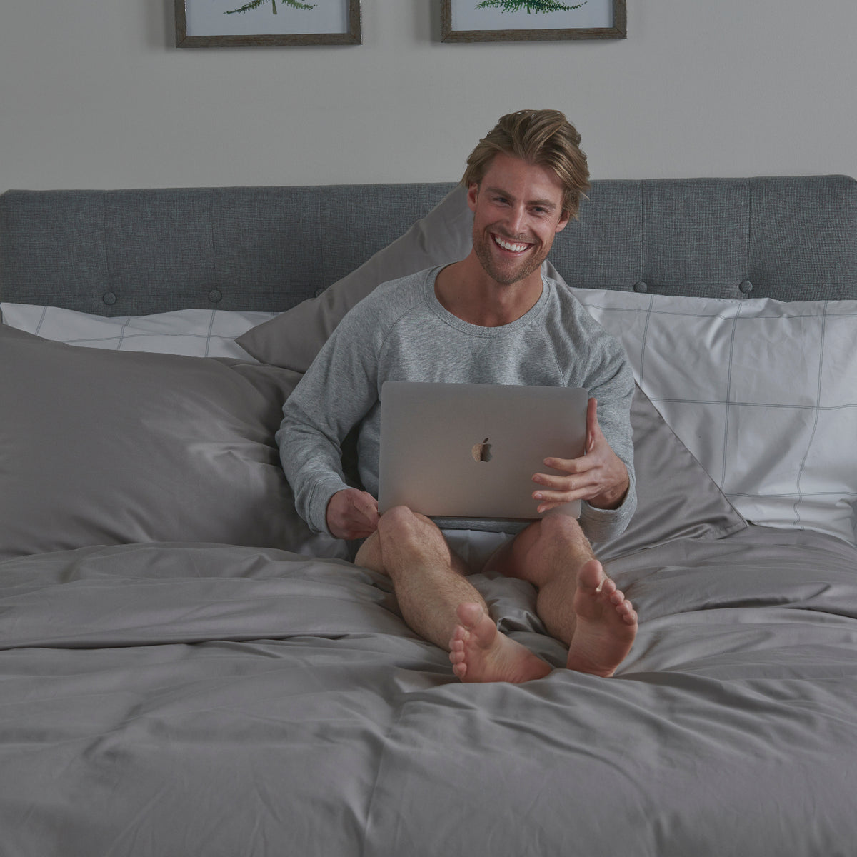 Man Sitting on Bed with Mac Laptop