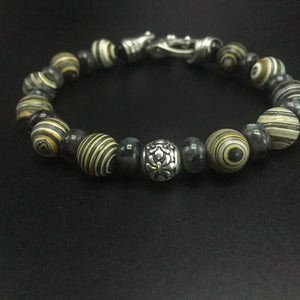 Yellow Malachite and gray Labradorite with a sterling silver center filagree bead and stainless steel clasp.