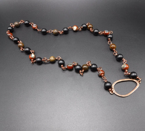16 inchnecklace contains: antique brass links, rosewood abalone Beads, black onyx beads, Bronzite, and copper pendant.