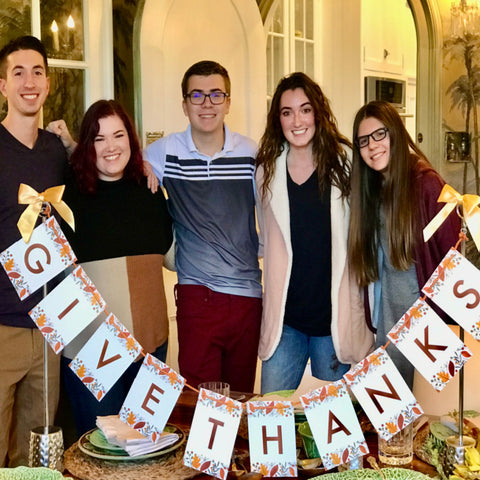 Family standing with Thanksgiving banner