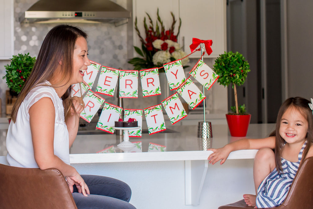 Merry Christmas banner with mother and daughter at kitchen island