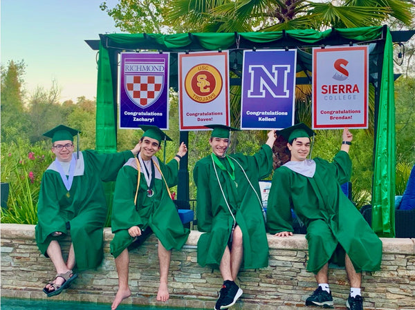 High school graduates sitting near a beautiful pool and pergola with college signs hanging above them