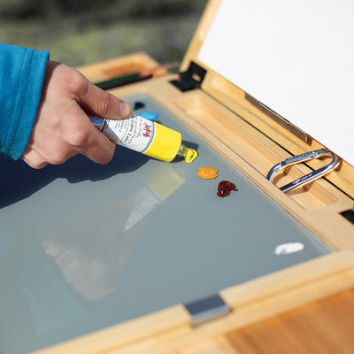 "u.go Plein Air Anywhere Pochade Box, 11"" x 14.5"" model, oil paint being squeezed out on gray tempered glass palette while plein air landscape painting"