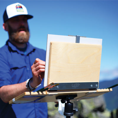 "u.go Plein Air Anywhere Pochade Box, 8.4"" x 11.25"" model, while plein air landscape painting atop a mountain"