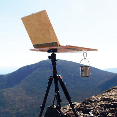 "u.go Plein Air Anywhere Pochade Box, 11"" x 14.5"" model, with u.go Cinch and u.go Carabiner on tripod while landscape plain air painting"