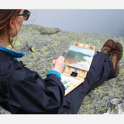 "u.go Plein Air Anywhere Pochade Box, 6"" x 8"" model, on lap atop a mountain while plein air landscape painting"