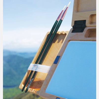 "u.go Plein Air Anywhere Side Tray 4"" x 8"" holding artist brushes while plein air landscape painting"