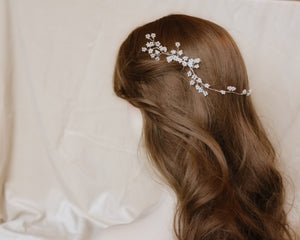 Delicate bridal hairstyle with cherry blossom hair piece