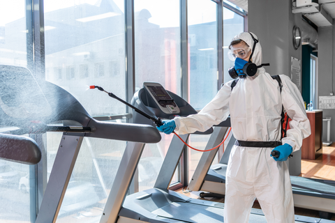 man with a protective suit and mask cleaning gym to prevent infection during coronavirus epidemic