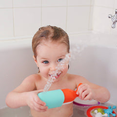 Girl playing in bath with Squirting Whale bath toy - spray of water jetting up