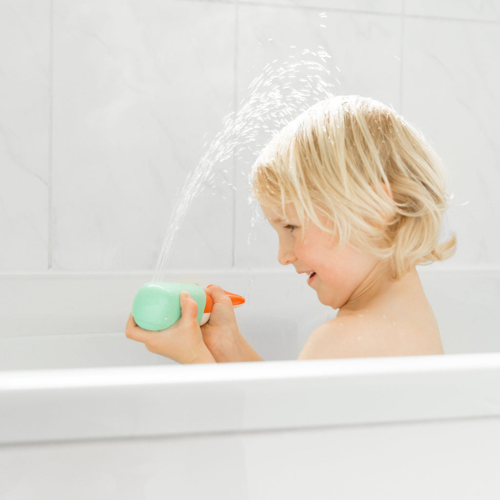 Child in the bath playing with Squirting Whale bath toy with a jet of water firing up over his head
