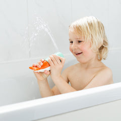 Boy laughing whilst playing in bath with Squirting Whale bath toy