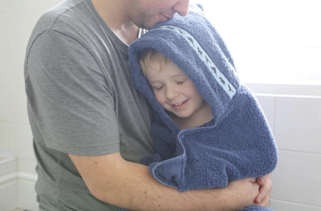 Child wearing navy blue hooded towel with Dinosaurs hooded towel enjoying a cuddle with his dad