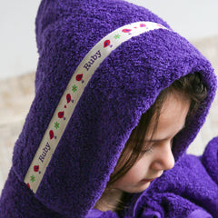 Child wearing purple hooded towel with personalised Birds trim