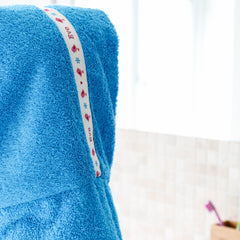 Child wearing turquoise hooded towel with personalised Birds trim