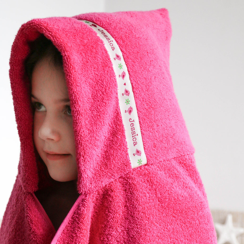 Child wearing pink hooded towel with personalised Birds trim