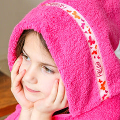 Child wearing a pink hooded towel with personalised Butterflies trim- Emily