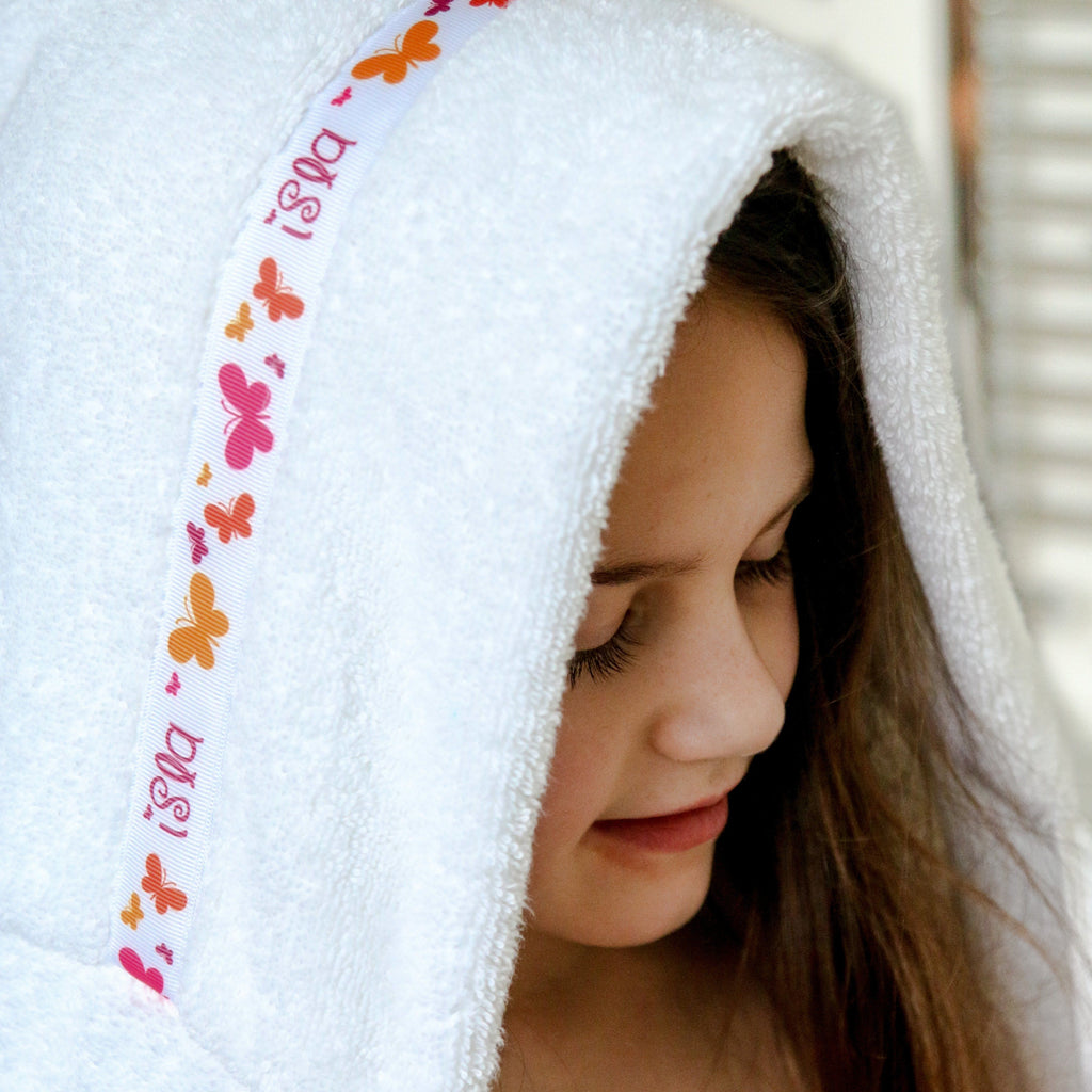 Child wearing a white hooded towel with personalised Butterflies trim- Isla