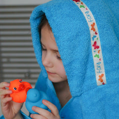 Child wearing a turquoise hooded towel with personalised Butterflies trim- Lucy