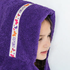 Child wearing a purple hooded towel with personalised Butterflies trim- Olivia