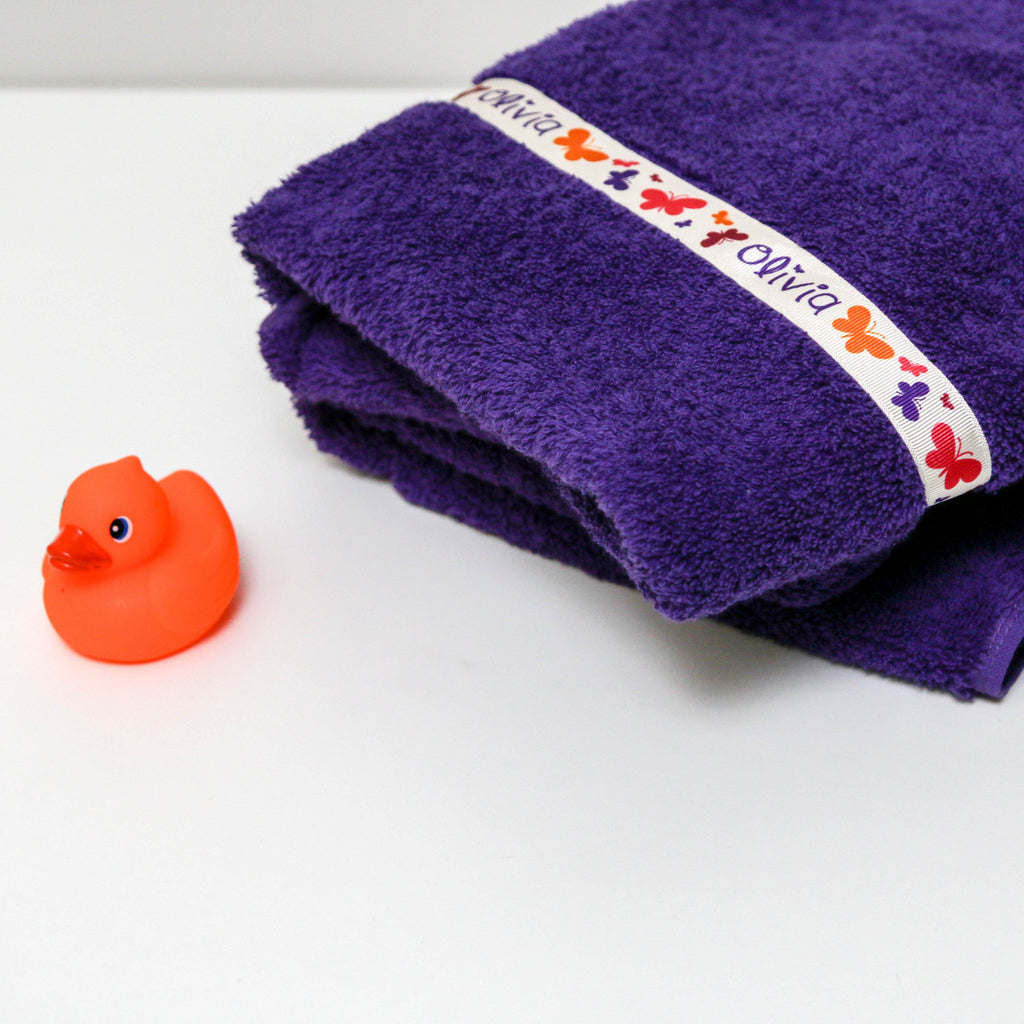 Purple  hooded towel with personalised Butterflies trim folded neatly next to rubber duck