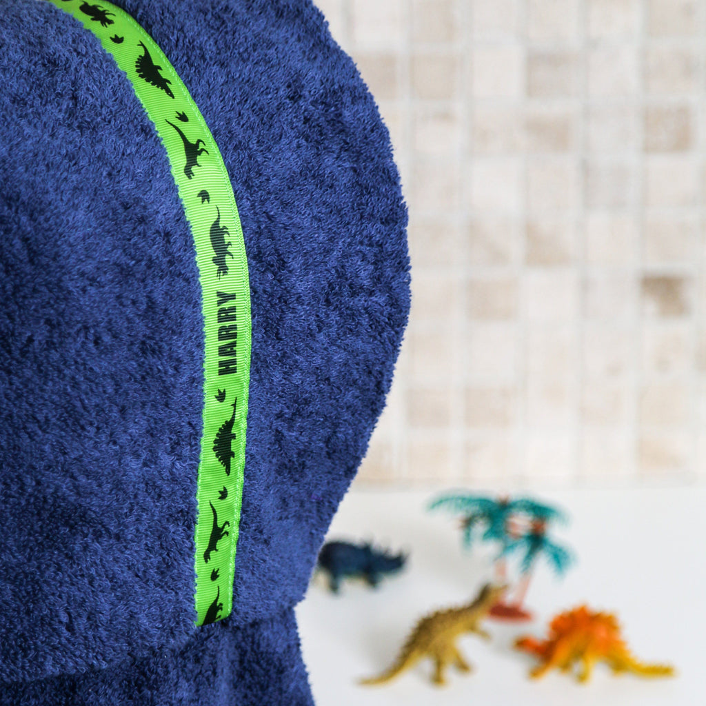 Child wearing navy blue hooded towel with personalised Dinosaurs trim (on green) with toy dinosaurs in the background