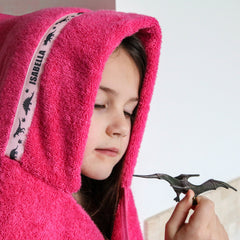 Child wearing pink hooded towel with personalised Dinosaurs trim, holdinig a toy dinosaur