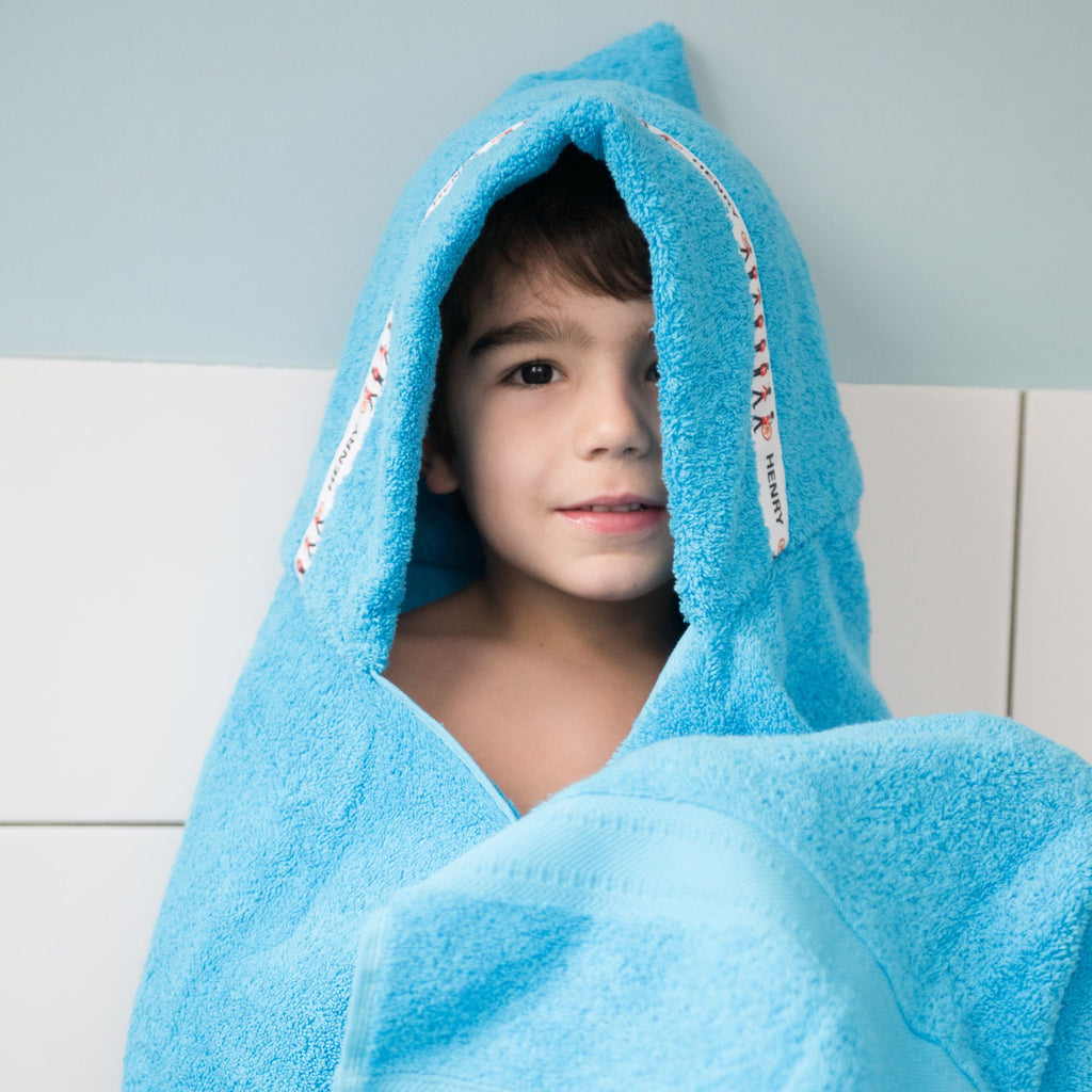 Child wearing a turquoise hooded towel with personalised Royal Guards trim