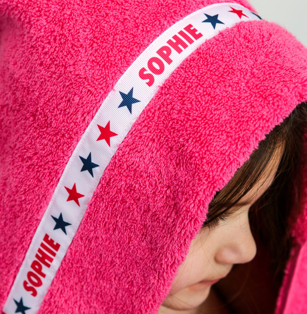 Child wearing a pink hooded towel with personalised Stars trim - Sophie