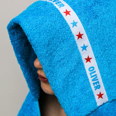 Child wearing a turquoise hooded towel with personalised Stars trim - Oliver
