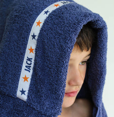 Child wearing a navy blue hooded towel with personalised Stars trim - Jack