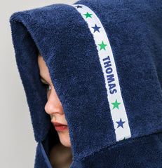 Child wearing a navy blue hooded towel with personalised Stars trim - Thomas